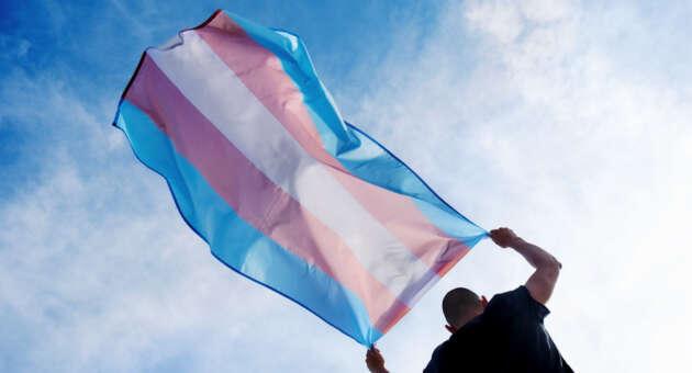 homem transgênero segurando bandeira trans