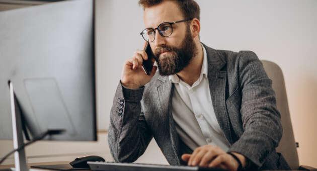 homem de paletó e óculos em escritório ao telefone